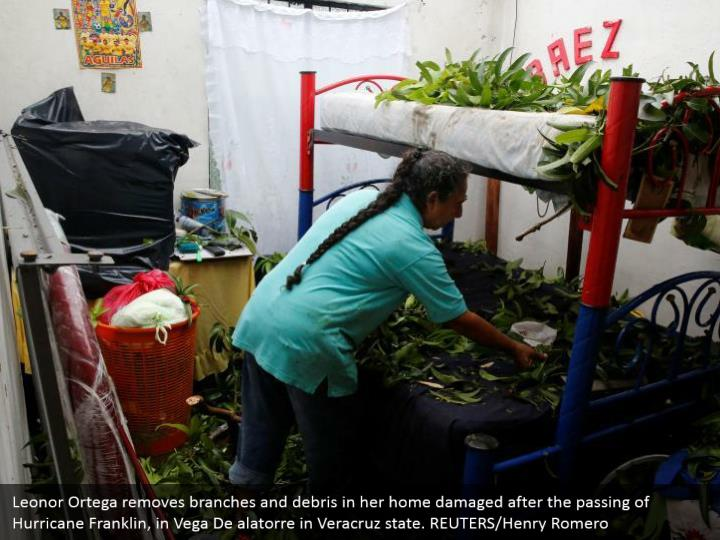 Leonor Ortega removes branches and debris in her home damaged after the passing of Hurricane Franklin, in Vega De alatorre in Veracruz state. REUTERS/Henry Romero