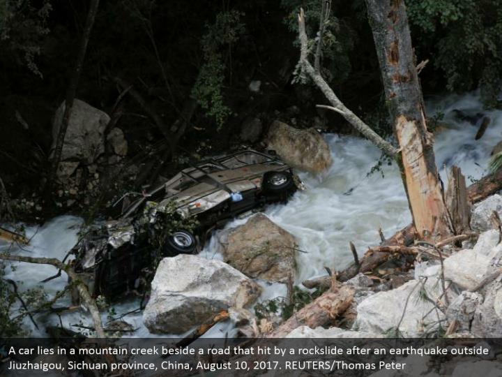 A car lies in a mountain creek beside a road that hit by a rockslide after an earthquake outside Jiuzhaigou, Sichuan province, China, August 10, 2017. REUTERS/Thomas Peter