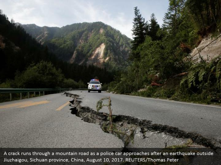 A crack runs through a mountain road as a police car approaches after an earthquake outside Jiuzhaigou, Sichuan province, China, August 10, 2017. REUTERS/Thomas Peter