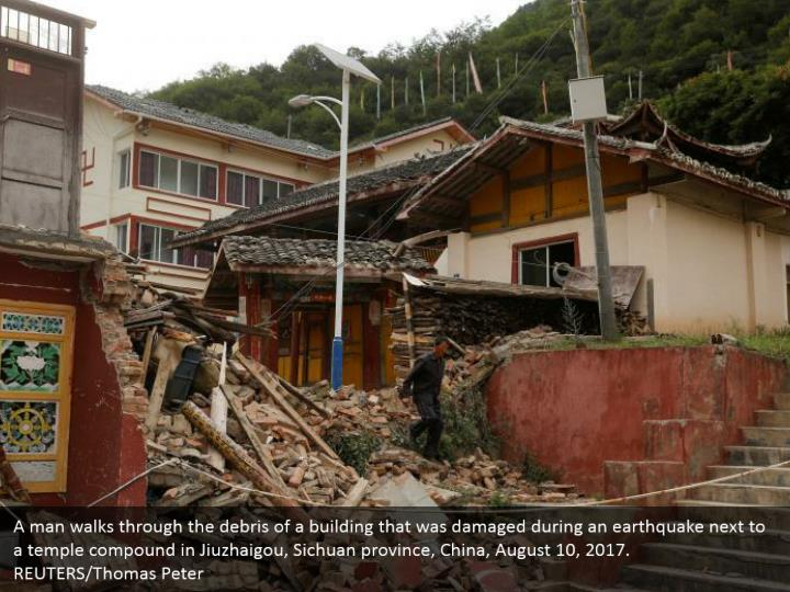 A man walks through the debris of a building that was damaged during an earthquake next to a temple compound in Jiuzhaigou, Sichuan province, China, August 10, 2017. REUTERS/Thomas Peter