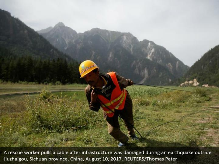 A rescue worker pulls a cable after infrastructure was damaged during an earthquake outside Jiuzhaigou, Sichuan province, China, August 10, 2017. REUTERS/Thomas Peter