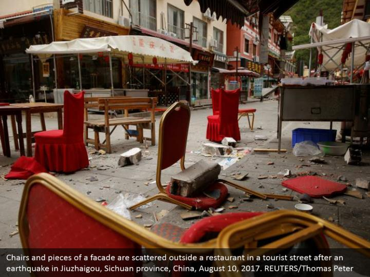Chairs and pieces of a facade are scattered outside a restaurant in a tourist street after an earthquake in Jiuzhaigou, Sichuan province, China, August 10, 2017. REUTERS/Thomas Peter