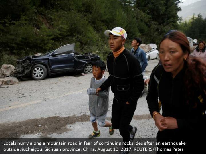 Locals hurry along a mountain road in fear of continuing rockslides after an earthquake outside Jiuzhaigou, Sichuan province, China, August 10, 2017. REUTERS/Thomas Peter