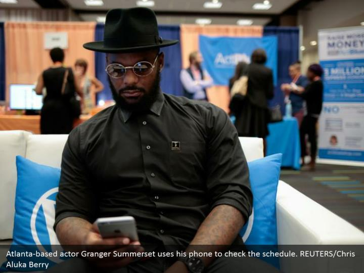 Atlanta-based actor Granger Summerset uses his phone to check the schedule. REUTERS/Chris Aluka Berry