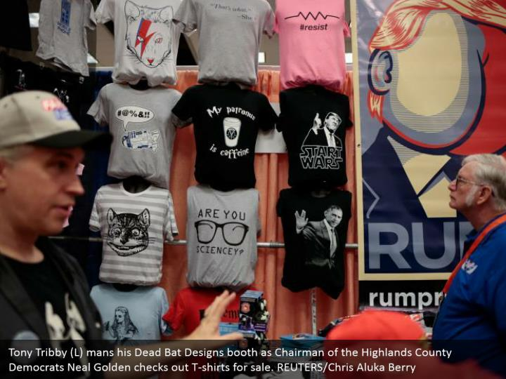 Tony Tribby (L) mans his Dead Bat Designs booth as Chairman of the Highlands County Democrats Neal Golden checks out T-shirts for sale. REUTERS/Chris Aluka Berry