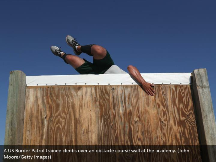 A US Border Patrol trainee climbs over an obstacle course wall at the academy. (John Moore/Getty Images)