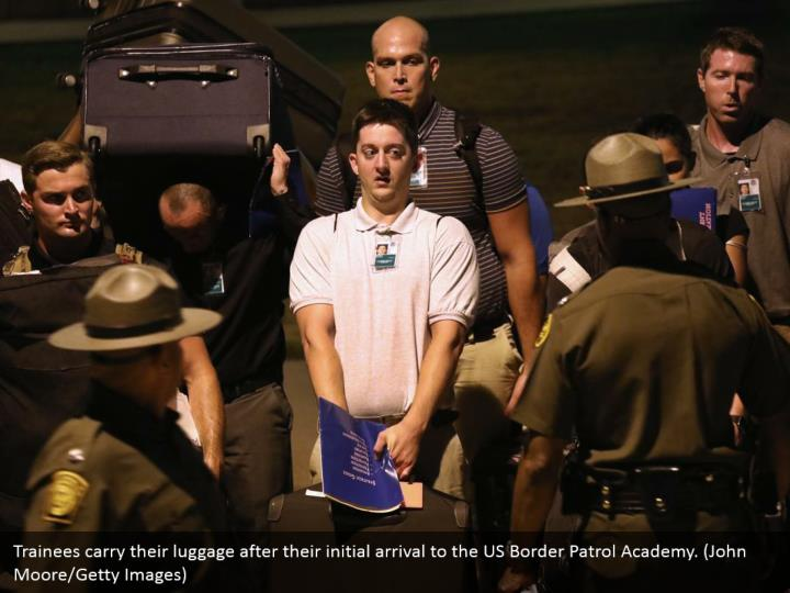 Trainees carry their luggage after their initial arrival to the US Border Patrol Academy. (John Moore/Getty Images)