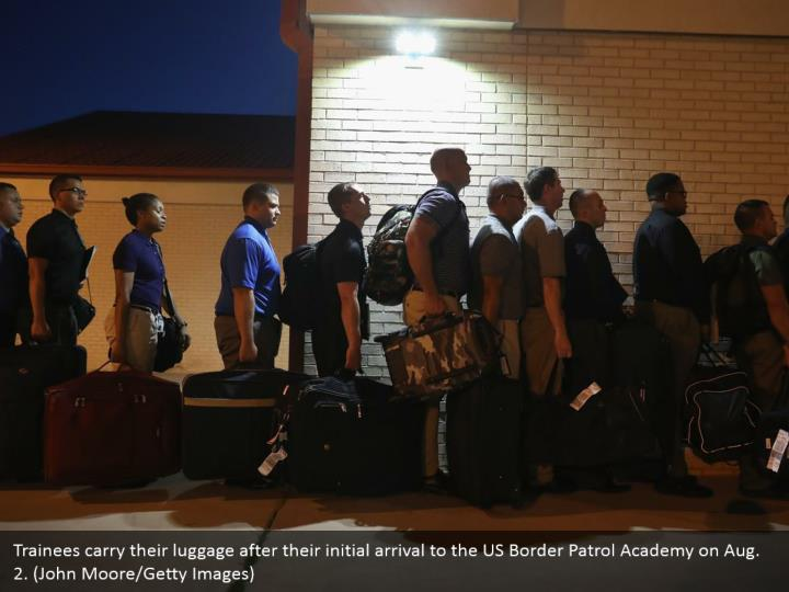 Trainees carry their luggage after their initial arrival to the US Border Patrol Academy on Aug. 2. (John Moore/Getty Images)