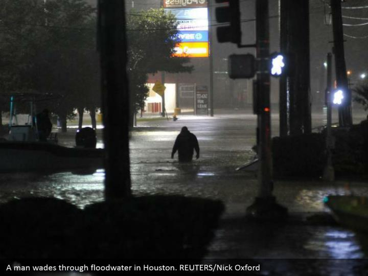A man wades through floodwater in Houston. REUTERS/Nick Oxford