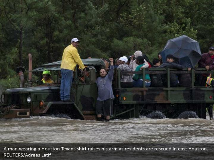 A man wearing a Houston Texans shirt raises his arm as residents are rescued in east Houston. REUTERS/Adrees Latif