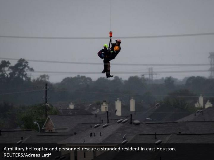 A military helicopter and personnel rescue a stranded resident in east Houston. REUTERS/Adrees Latif