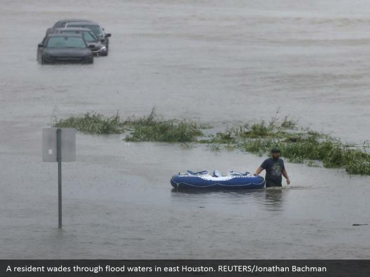 A resident wades through flood waters in east Houston. REUTERS/Jonathan Bachman