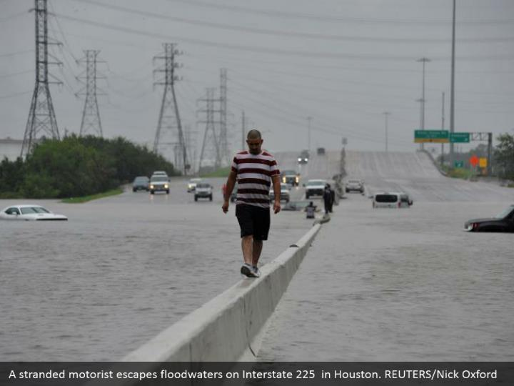 A stranded motorist escapes floodwaters on Interstate 225  in Houston. REUTERS/Nick Oxford