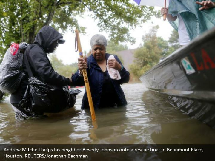 Andrew Mitchell helps his neighbor Beverly Johnson onto a rescue boat in Beaumont Place, Houston. REUTERS/Jonathan Bachman