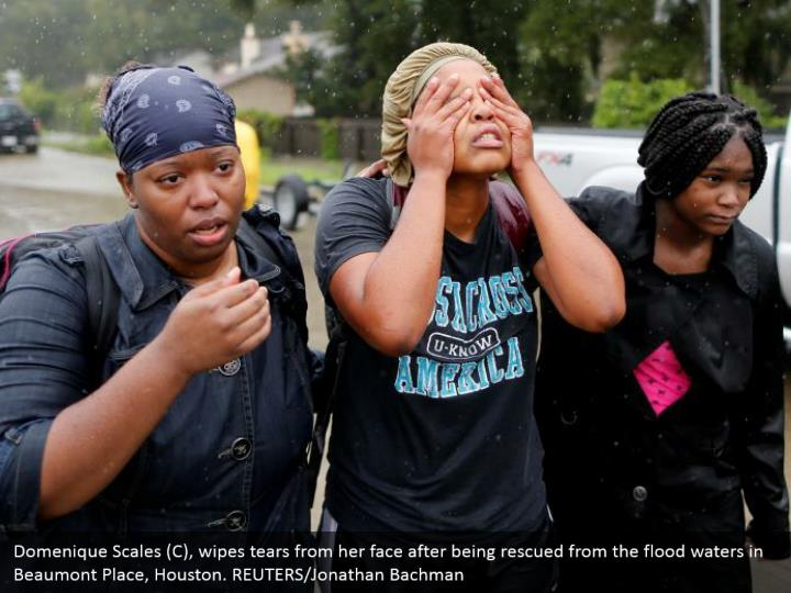 Domenique Scales (C), wipes tears from her face after being rescued from the flood waters in Beaumont Place, Houston. REUTERS/Jonathan Bachman