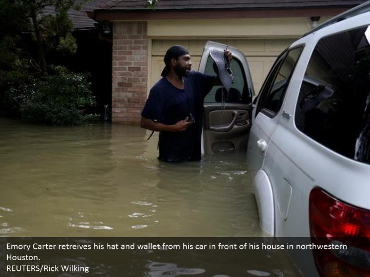 Emory Carter retreives his hat and wallet from his car in front of his house in northwestern Houston.  REUTERS/Rick Wilking