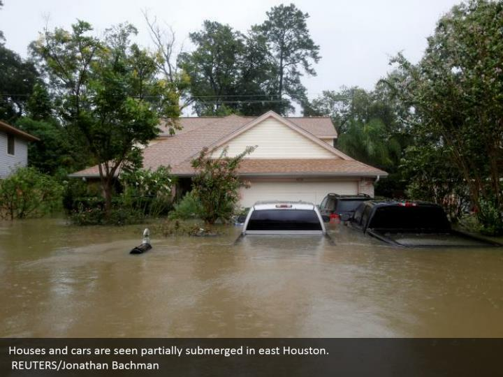Houses and cars are seen partially submerged in east Houston.  REUTERS/Jonathan Bachman