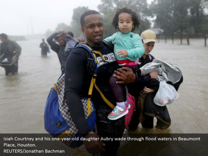 Isiah Courtney and his one-year-old daughter Aubry wade through flood waters in Beaumont Place, Houston.  REUTERS/Jonathan Bachman