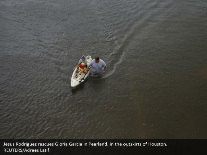 Jesus Rodriguez rescues Gloria Garcia in Pearland, in the outskirts of Houston.  REUTERS/Adrees Latif