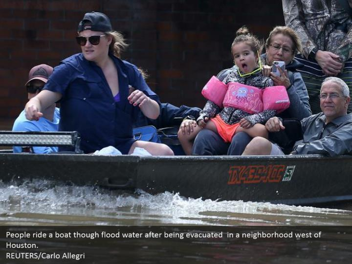 People ride a boat though flood water after being evacuated  in a neighborhood west of Houston.  REUTERS/Carlo Allegri