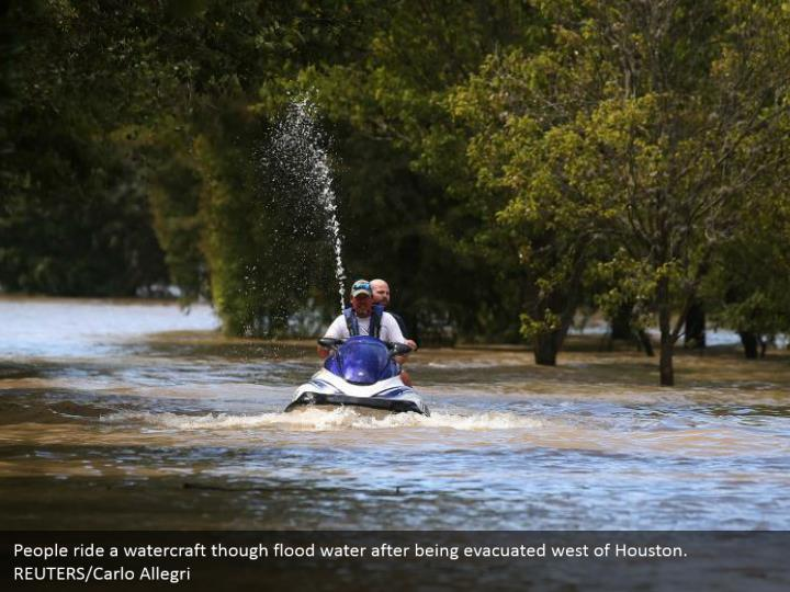 People ride a watercraft though flood water after being evacuated west of Houston.  REUTERS/Carlo Allegri