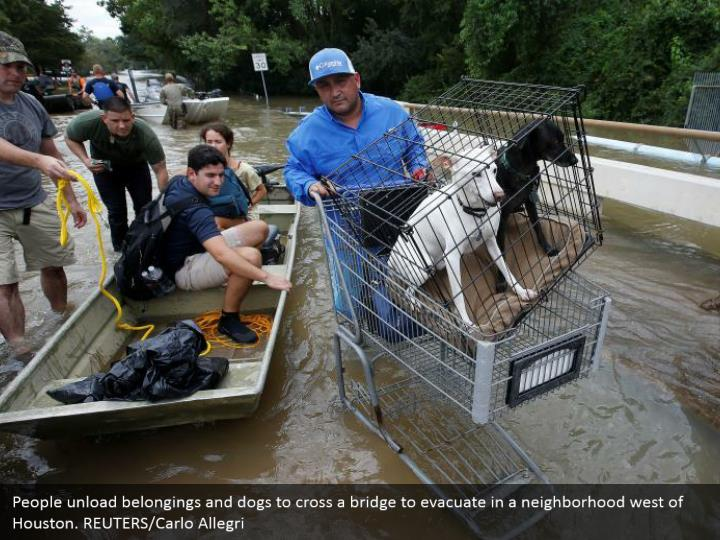 People unload belongings and dogs to cross a bridge to evacuate in a neighborhood west of Houston. REUTERS/Carlo Allegri