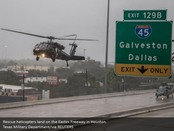 Rescue helicopters land on the Eastex Freeway in Houston.  Texas Military Department/via REUTERS