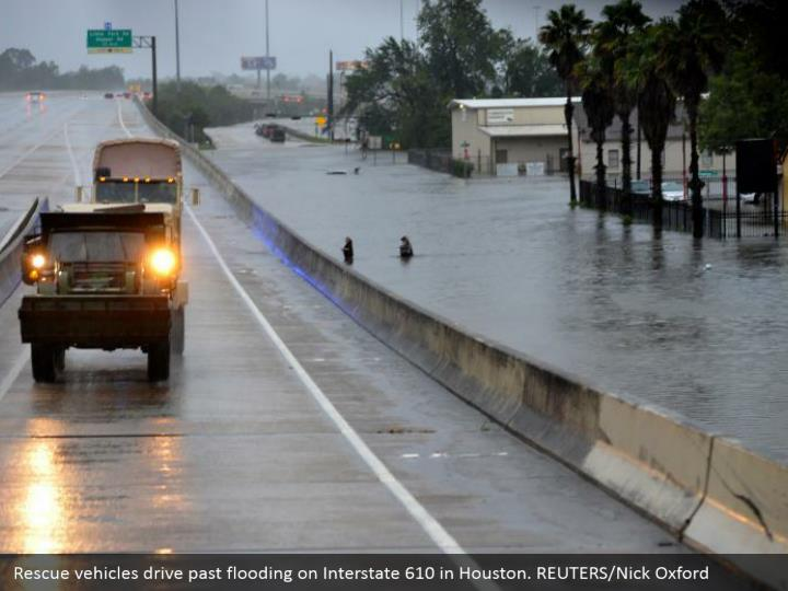 Rescue vehicles drive past flooding on Interstate 610 in Houston. REUTERS/Nick Oxford