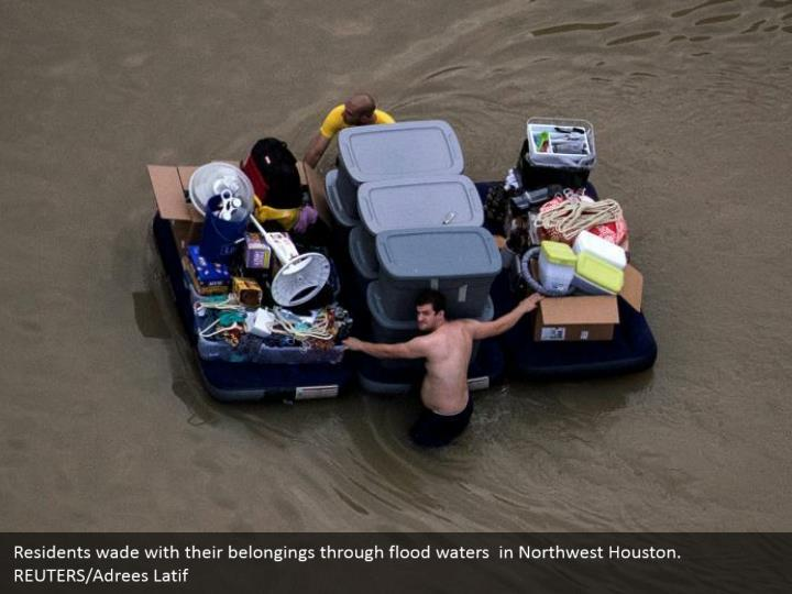 Residents wade with their belongings through flood waters  in Northwest Houston. REUTERS/Adrees Latif
