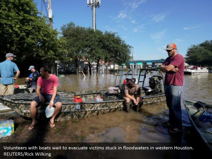 Volunteers with boats wait to evacuate victims stuck in floodwaters in western Houston.  REUTERS/Rick Wilking