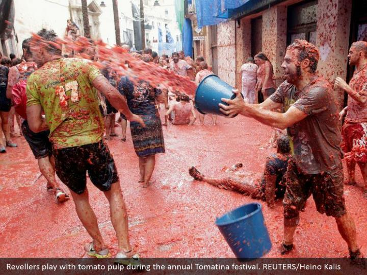 Revellers play with tomato pulp during the annual Tomatina festival. REUTERS/Heino Kalis