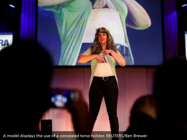 A model displays the use of a concealed torso holster. REUTERS/Ben Brewer