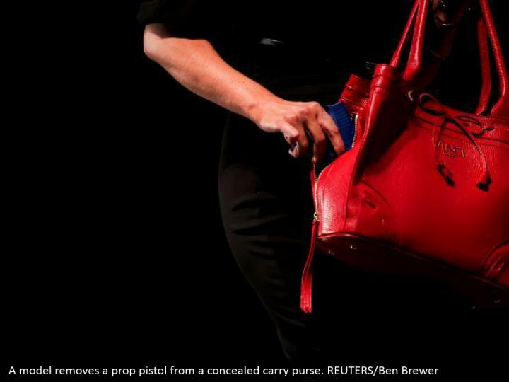 A model removes a prop pistol from a concealed carry purse. REUTERS/Ben Brewer