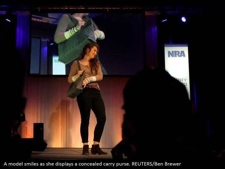A model smiles as she displays a concealed carry purse. REUTERS/Ben Brewer
