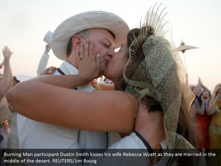 Burning Man participant Dustin Smith kisses his wife Rebecca Wyatt as they are married in the middle of the desert. REUTERS/Jim Bourg