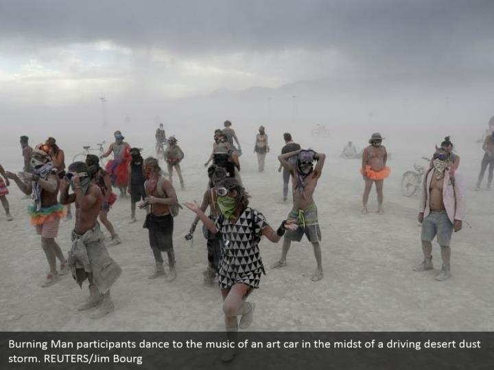 Burning Man participants dance to the music of an art car in the midst of a driving desert dust storm. REUTERS/Jim Bourg