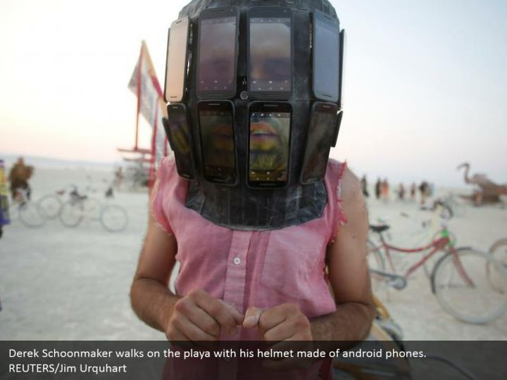 Derek Schoonmaker walks on the playa with his helmet made of android phones. REUTERS/Jim Urquhart