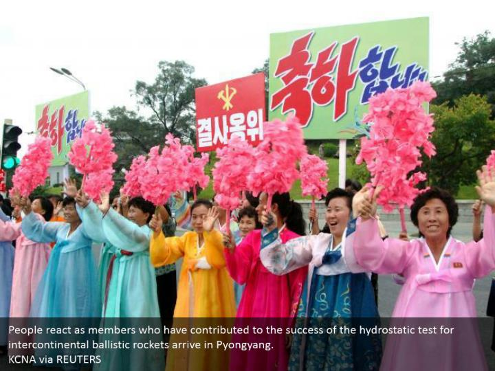 People react as members who have contributed to the success of the hydrostatic test for intercontinental ballistic rockets arrive in Pyongyang.  KCNA via REUTERS