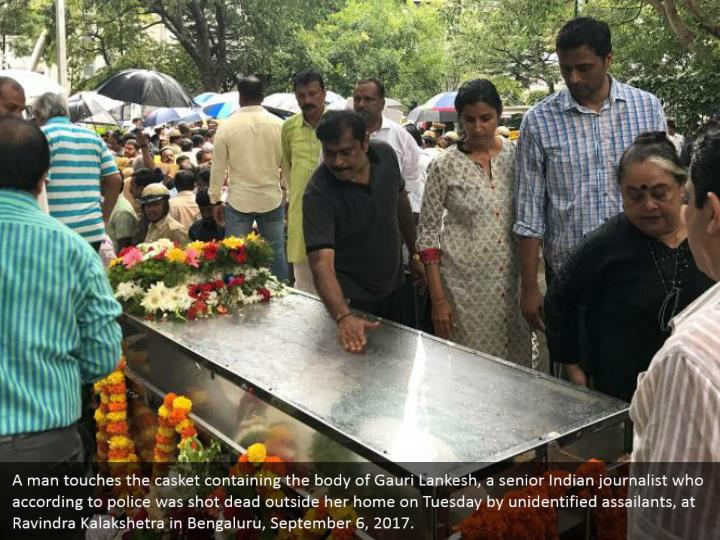 A man touches the casket containing the body of Gauri Lankesh, a senior Indian journalist who according to police was shot dead outside her home on Tuesday by unidentified assailants, at Ravindra Kalakshetra in Bengaluru, September 6, 2017.
