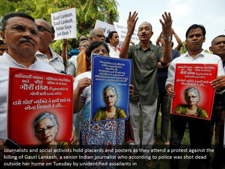 Journalists and social activists hold placards and posters as they attend a protest against the killing of Gauri Lankesh, a senior Indian journalist who according to police was shot dead outside her home on Tuesday by unidentified assailants in