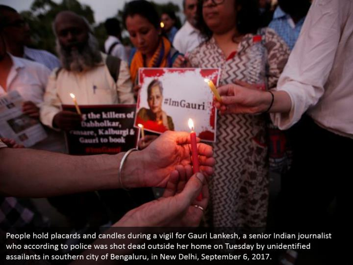 People hold placards and candles during a vigil for Gauri Lankesh, a senior Indian journalist who according to police was shot dead outside her home on Tuesday by unidentified assailants in southern city of Bengaluru, in New Delhi, September 6, 2017.