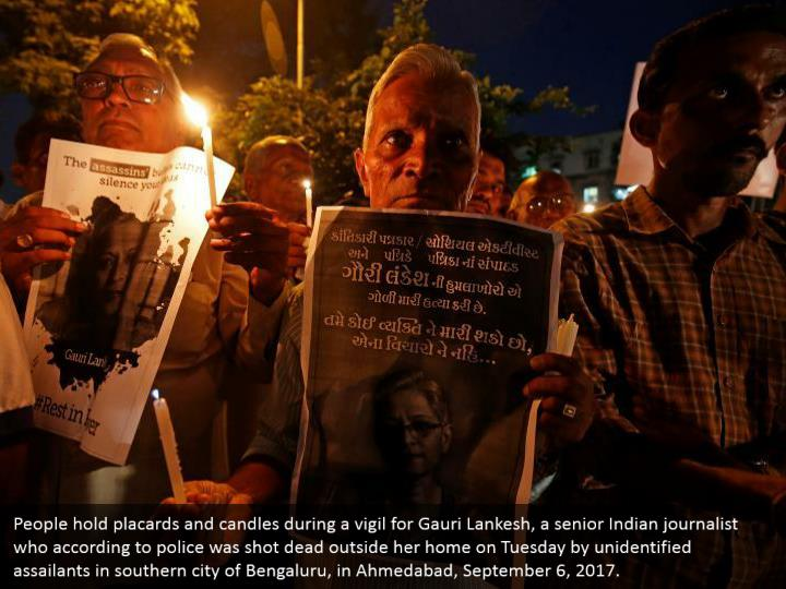 People hold placards and candles during a vigil for Gauri Lankesh, a senior Indian journalist who according to police was shot dead outside her home on Tuesday by unidentified assailants in southern city of Bengaluru, in Ahmedabad, September 6, 2017.