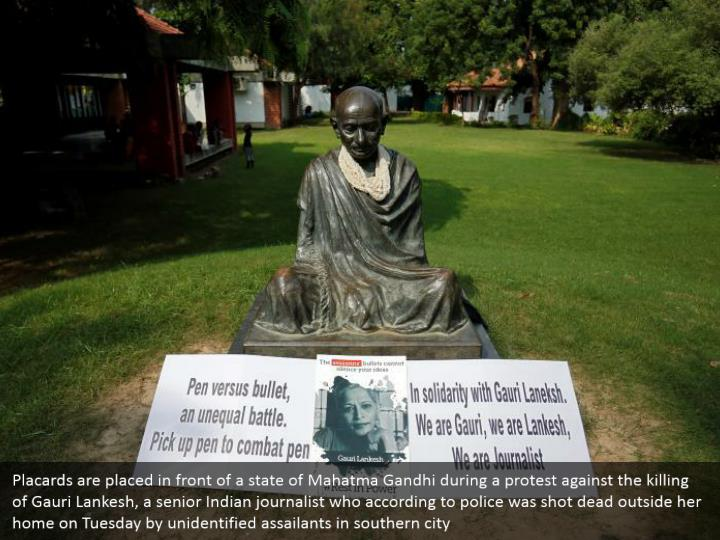 Placards are placed in front of a state of Mahatma Gandhi during a protest against the killing of Gauri Lankesh, a senior Indian journalist who according to police was shot dead outside her home on Tuesday by unidentified assailants in southern city
