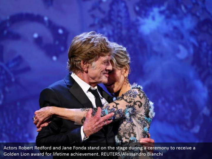 Actors Robert Redford and Jane Fonda stand on the stage during a ceremony to receive a Golden Lion award for lifetime achievement. REUTERS/Alessandro Bianchi