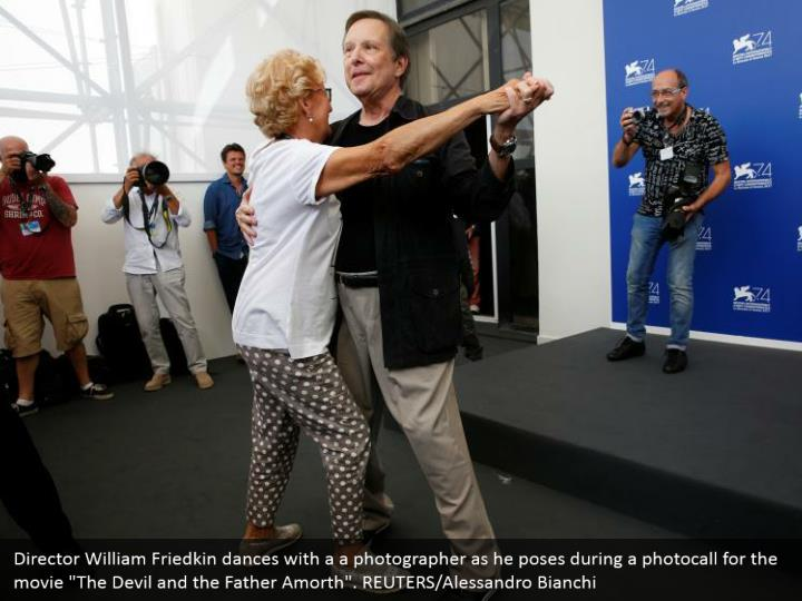 "Director William Friedkin dances with a a photographer as he poses during a photocall for the movie ""The Devil and the Father Amorth"". REUTERS/Alessandro Bianchi"