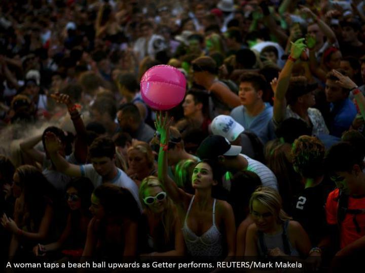 A woman taps a beach ball upwards as Getter performs. REUTERS/Mark Makela