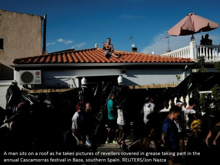 A man sits on a roof as he takes pictures of revellers covered in grease taking part in the annual Cascamorras festival in Baza, southern Spain. REUTERS/Jon Nazca