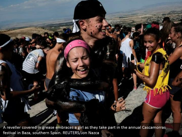 A reveller covered in grease embraces a girl as they take part in the annual Cascamorras festival in Baza, southern Spain. REUTERS/Jon Nazca