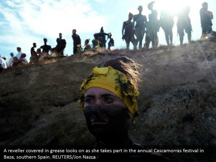 A reveller covered in grease looks on as she takes part in the annual Cascamorras festival in Baza, southern Spain. REUTERS/Jon Nazca