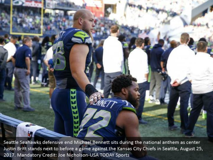 Seattle Seahawks defensive end Michael Bennett sits during the national anthem as center Justin Britt stands next to before a game against the Kansas City Chiefs in Seattle, August 25, 2017. Mandatory Credit: Joe Nicholson-USA TODAY Sports
